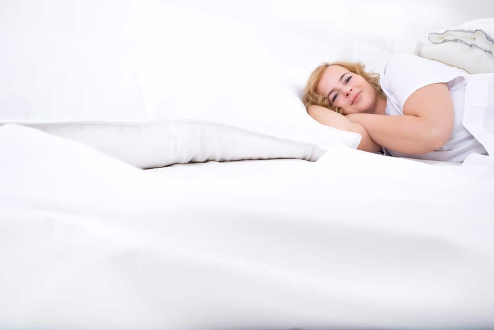 A heavy woman sleeping in her bed
